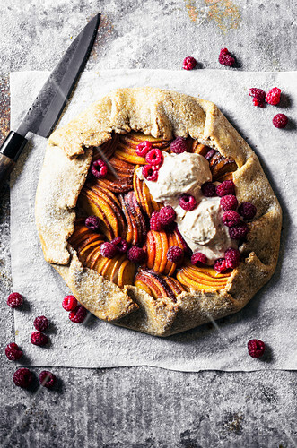 Peach, apricot, and nectarine galette with ice cream and raspberries