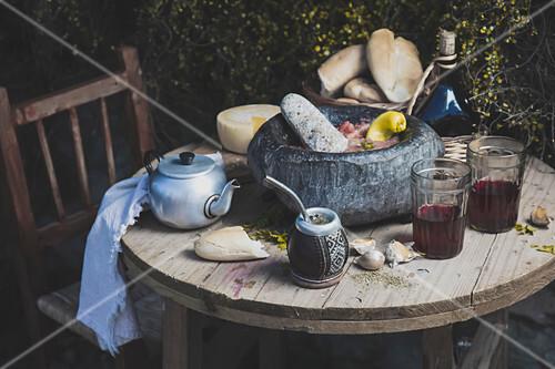 Tisch mit chilenischen Gerichten und Getränken: Chancho en piedra (Schweinefleischgericht mit Tomatensauce)