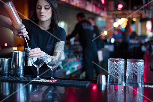 A bartender mixing cocktails at a bar