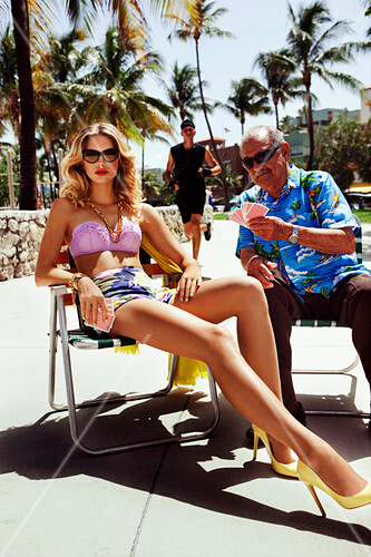 A young blonde woman wearing a bikini sitting on a chair and playing cards with an older man