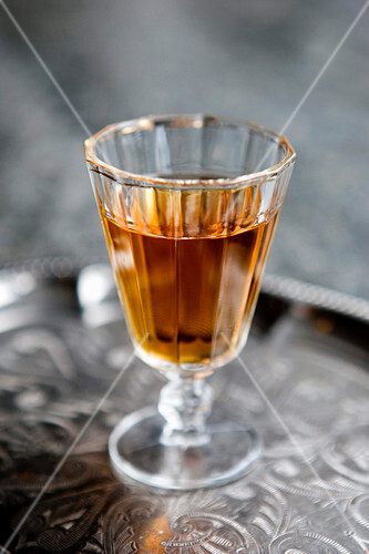 A glass of rum on a silver tray