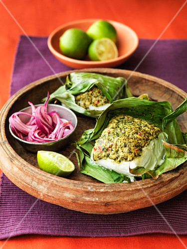 Indian spiced fish wrapped in banana leafs with red onion