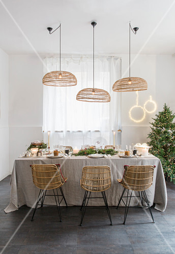 Cane lampshades above festively set dining table in natural shades