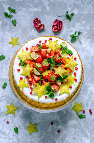 Cake decorated with strawberries, limequat, star fruit and mint