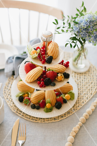 Berries and madeleines on cake stand on table festively set for afternoon coffee