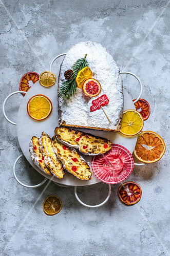 Christmas stollen on an openwork stand with citrus chips, decorated in a Christmas design