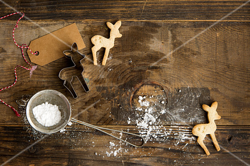 Festive Christmas deer shaped biscuits on a rustic board with cookie cutter, icing sugar in sifter and gift label