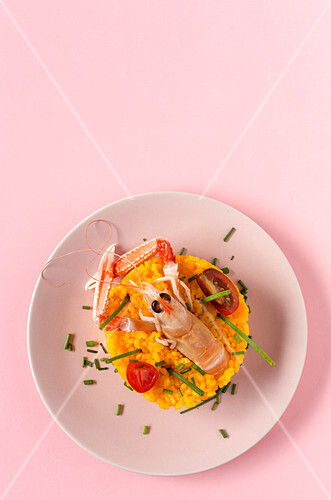 Homemade rice with crayfish and prawns on pink background