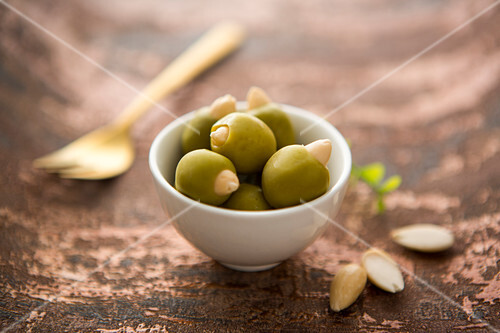 A bowl of green olives filled with almonds