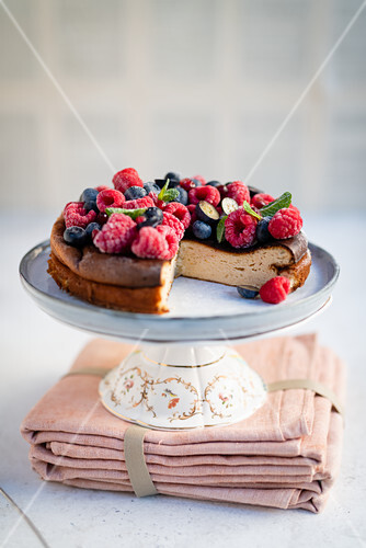 Cheesecake with berries on a cake stand, sliced