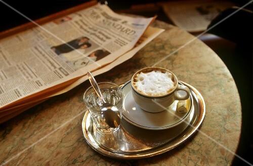 tasse cappuccino glas wasser zeitung auf kaffeehaustisch bild kaufen 141892 stockfood. Black Bedroom Furniture Sets. Home Design Ideas