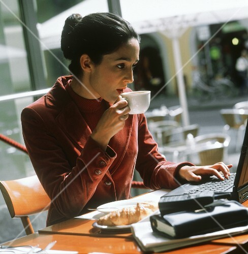 Businesswoman in café using laptop with coffee cup & croissant