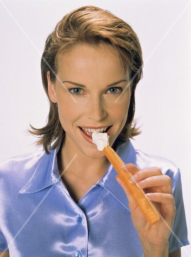 Young woman eating carrot with cream cheese dip