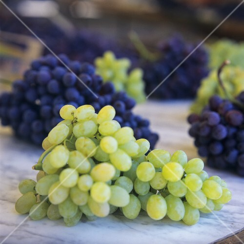 Green grapes on marble platter, red & green grapes behind