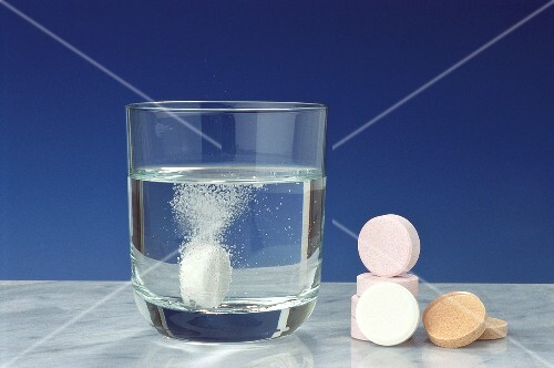 Soluble vitamin tablet in glass & vitamin tablets beside it