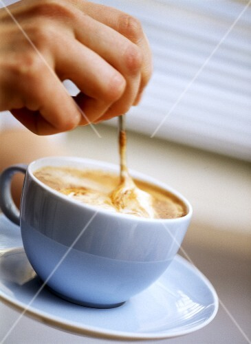 Stirring cappuccino in pale-blue cup