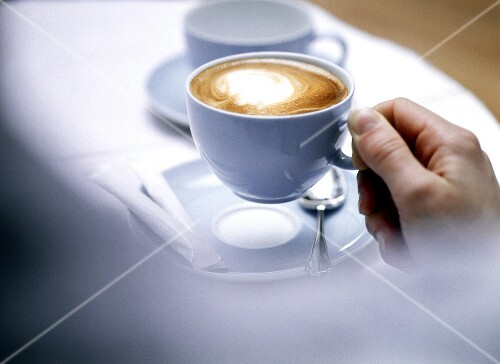 Hand holding cappuccino in pale-blue cup