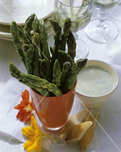 Fresh green asparagus stalks with herb dip