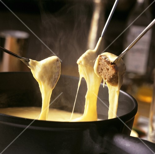 Cheese fondue with bread cubes on fondue forks