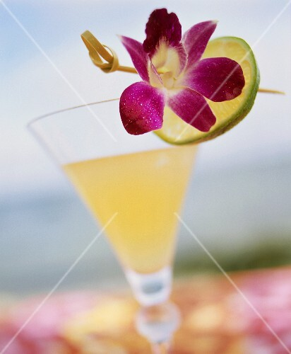 A glass of Daiquiri, garnished with lime peel and flower