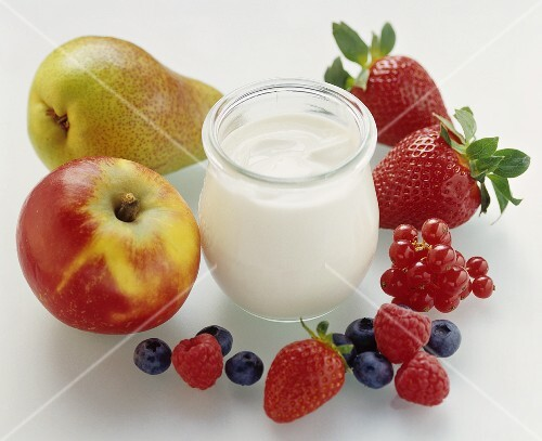 A jar of natural yoghurt surrounded by berries & fruit