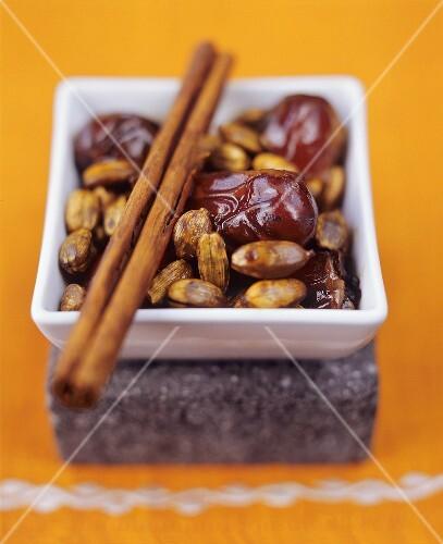 Bowl of dates, cardamom, cinnamon sticks on top