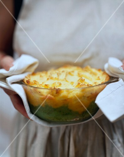 Woman holding glass dish with baked layered mashed potato