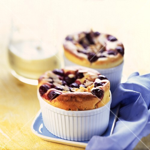 Two blueberry souffles in souffle dishes