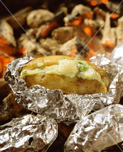 Baked potatoes with cheese filling on glowing charcoal