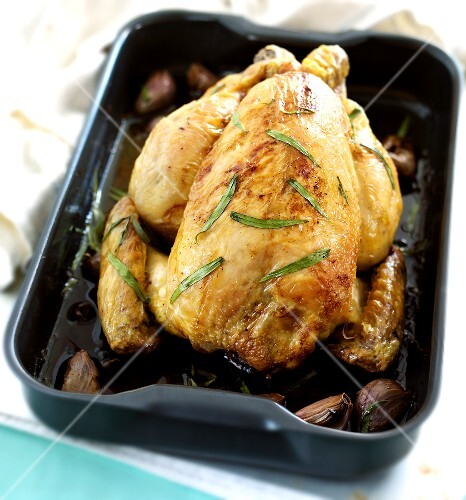 Baked chicken with tarragon and garlic in roasting dish