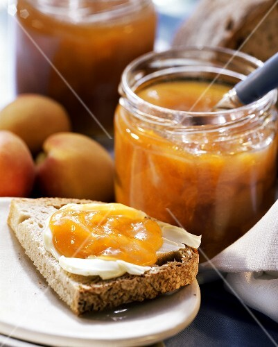 Peach jam on bread and in preserving jar