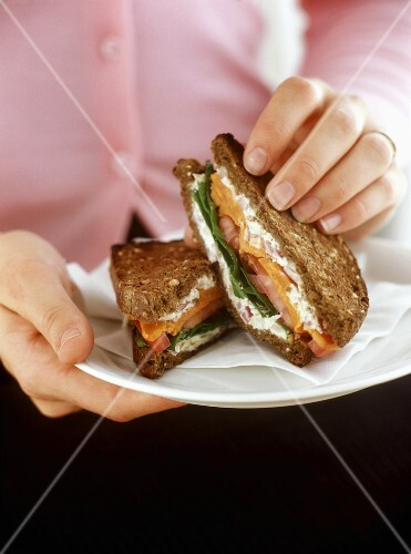 Hand holding wholemeal sweet potato, salad and  ricotta sandwich
