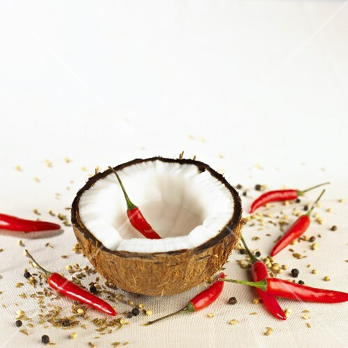 Coconut half with chili peppers and spices