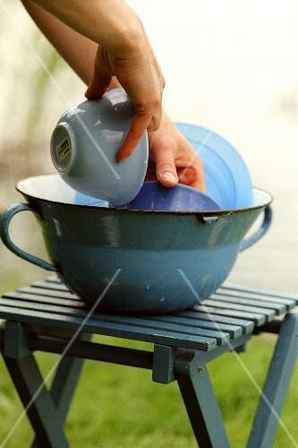 Geschirr abwaschen in blauer Schüssel auf Campinghocker