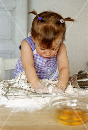 Small girl kneading dough ingredients
