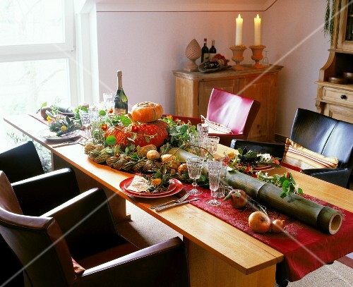 Autumnal dining table decorated with pumpkin and a long bamboo stem