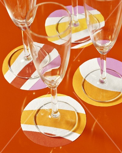 Four champagne glasses on coloured coasters