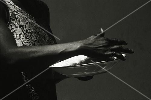 Eine schwarzafrikanische Frau hält eine Schale mit Reis