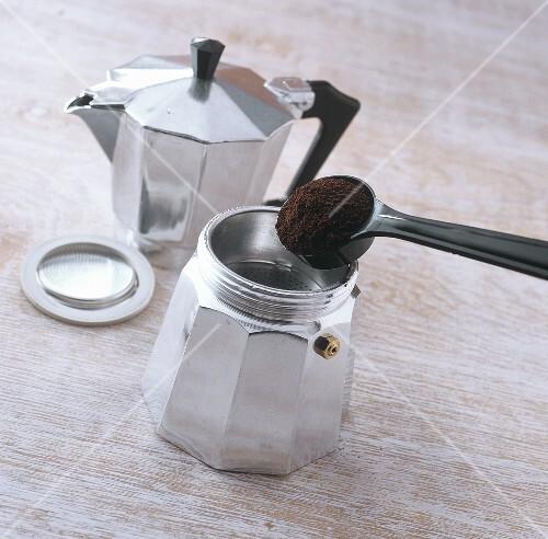 Making espresso: filling strainer with coffee powder