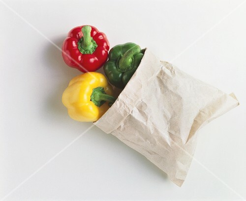 Three peppers (red, yellow, green) in paper bag
