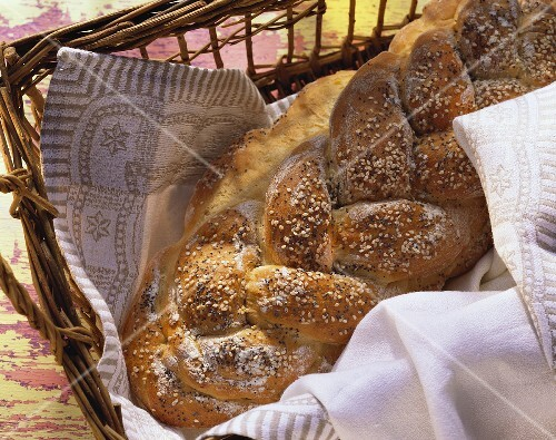 Bread plait with poppy seeds & sesame on cloth in basket