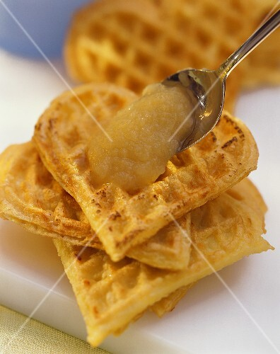 Potato waffles with apple puree on spoon above waffles