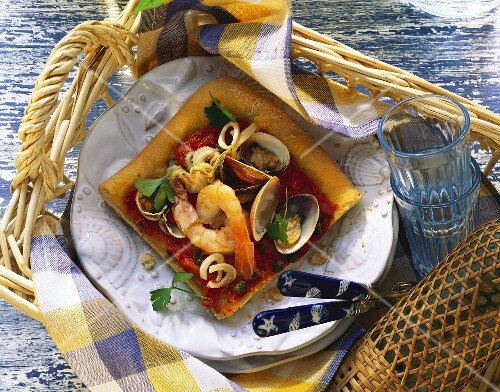 Piece of pizza with seafood on plate on wicker tray