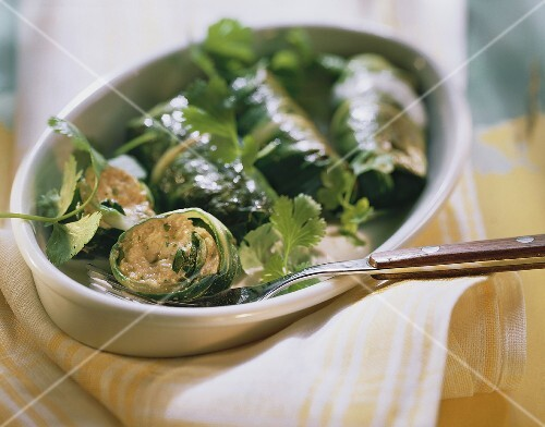Stuffed chard parcels (one cut open) in a gratin dish