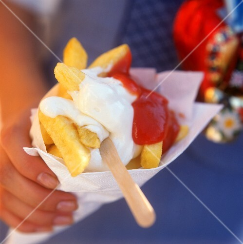 Hand holding a bag of chips with mayonnaise and ketchup