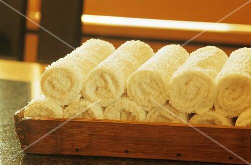 Oshibori (hot, moist, cloths for freshening up) in wooden tray