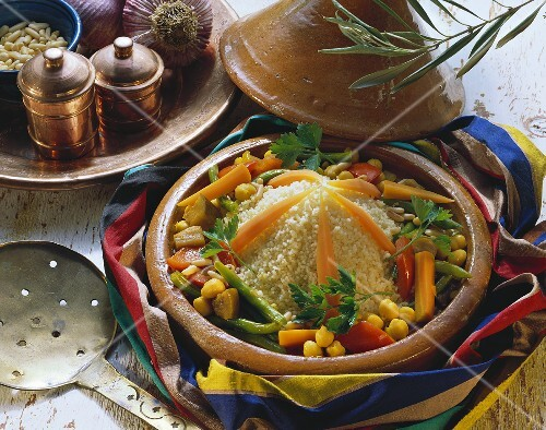 Couscous with vegetables in clay dish; pine nuts; garlic