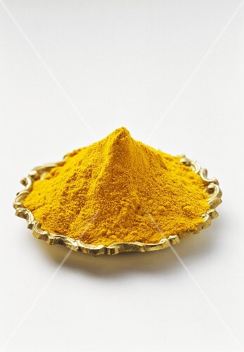 Turmeric powder on gold-coloured plate