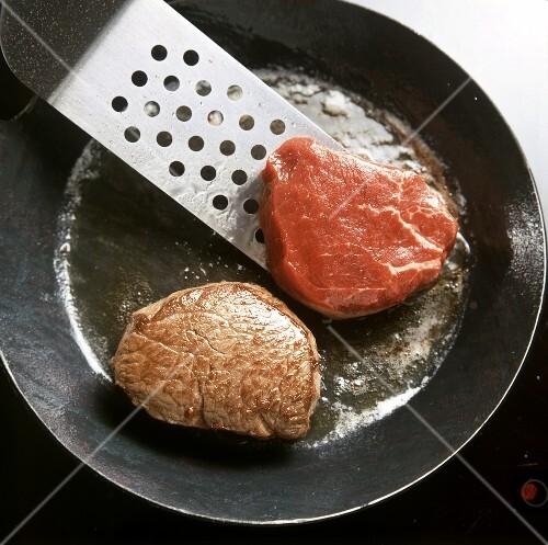 Frying fillet steak in iron pan