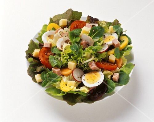 Mixed salad leaves with vegetables, egg, ham in dish